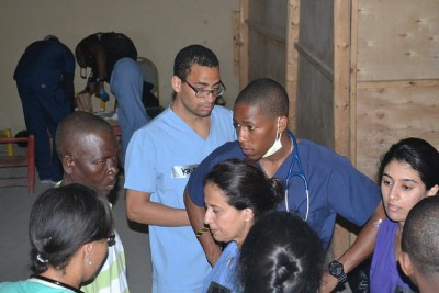 Yves-Dany Accilien (dark blue scrubs) and other students at the makeshift clinic in Cap-Haitien.