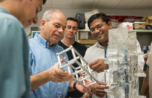 Dr. Tansel and Shinde examine CubeSAT component with team members