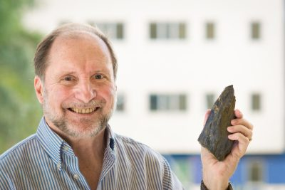 FIU geoscientist Gren Draper holds up his favorite rock, the Blueschist rock that set his career in motion.