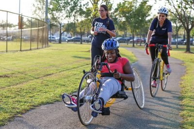 FIU student Nancy Antoine learns to ride a hand cycle through a recreational therapy program at Tamiami Park.