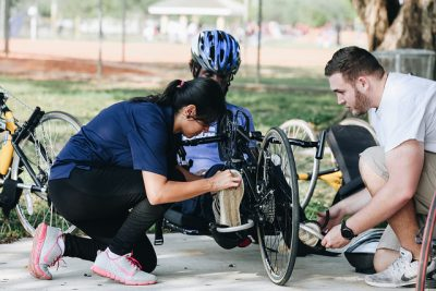Recreational Therapy Instructor Tania Santiago Perez adjusts the leg straps for one of the hand cycling participants.