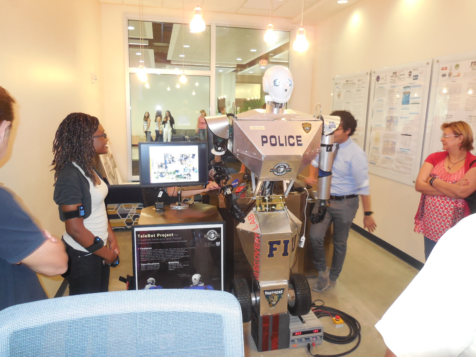 Students examine the initial prototype of the TeleBot created in FIU's Discovery Lab.