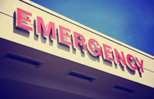 the front entrance sign to an emergency room department in a city hospital toned with a retro vintage instagram filter effect app or action