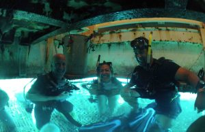 Jim Fourqurean, Aileen Soto and Christian Lopes pose under the wet porch of Aquarius.