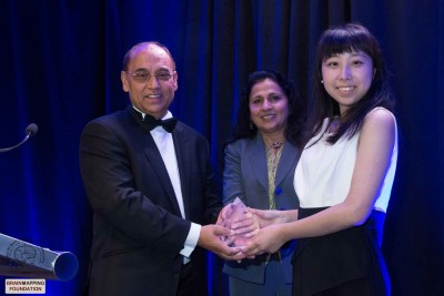 Mr. and Mrs. Sidhu present Fang with award.