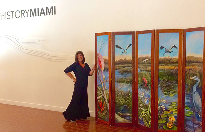 "Patricia Cummins, '79, was named Florida's Elementary Art Educator of the year by the Florida Art Education Association. Here she is pictured with her oil on canvas painting, ""Everglades Dream,"" part of the permanent collection of the Tropical Audubon Society."