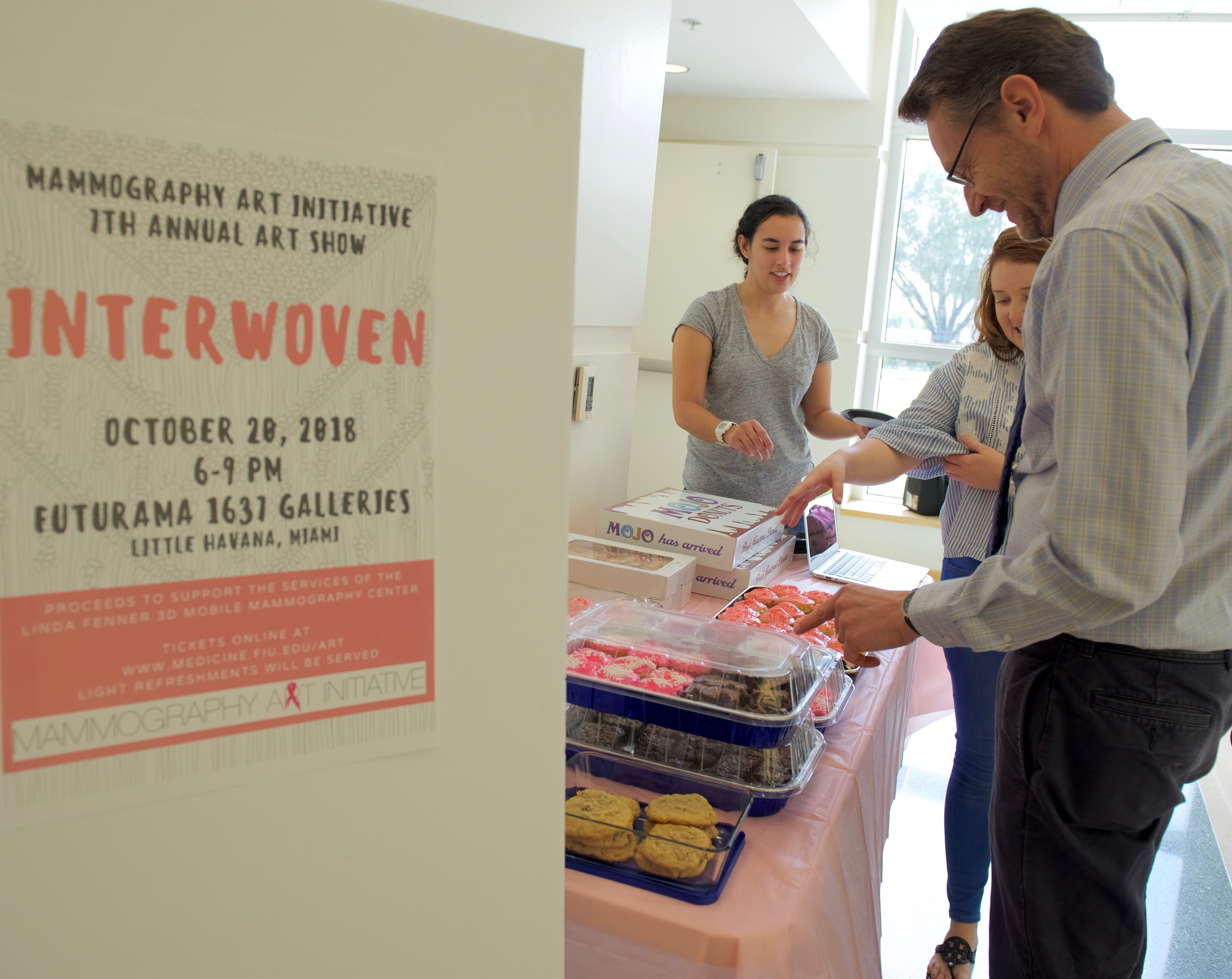 Dr. Gregory Schneider decides he'll take a cupcake at a bake sale where HWCOM students are also raising funds for the Mammography Art Initiative.