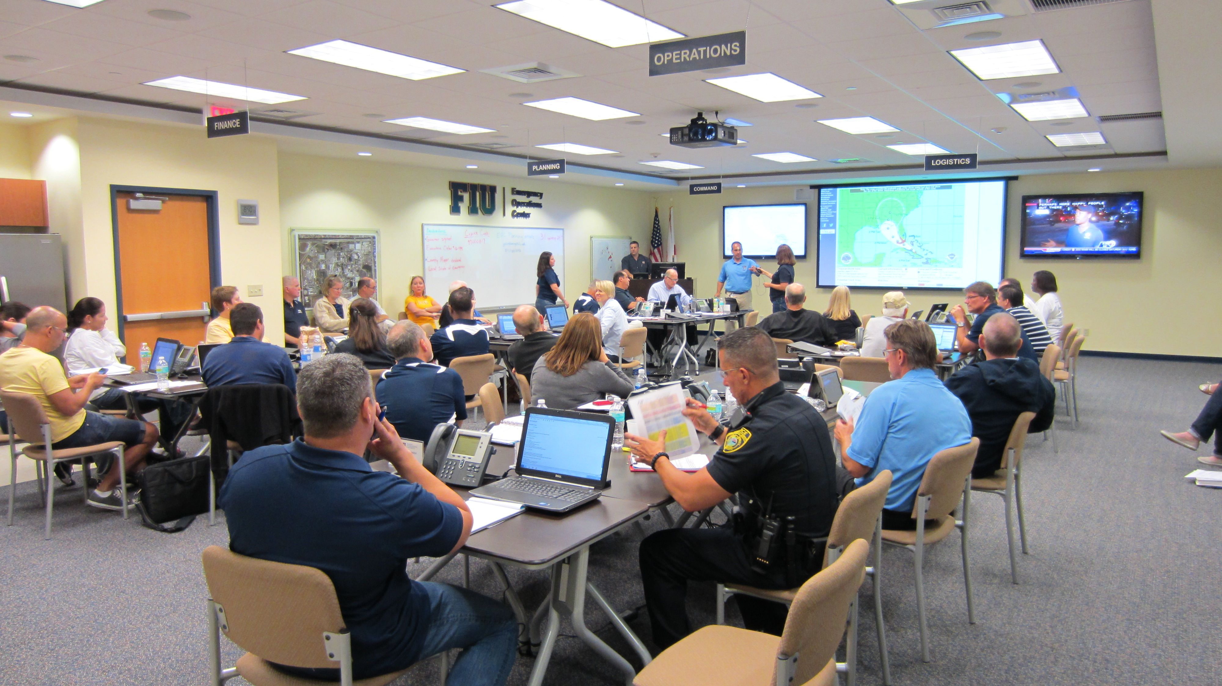 University leaders and personnel from the Department of Emergency Management share information and monitor conditions during the the South Florida approach of Tropical Storm Isaac.
