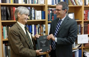 FIU Law Professor Jose Gabilondo (left) presents Michael Gillespie (right) of the Center for the Humanities in an Urban Environment with a copy of his latest book.