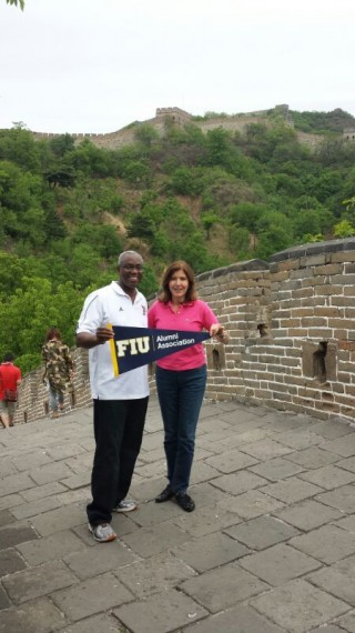 Trustee Gerald Grant Jr. '78, MBA '89 (left) and Trustee Claudia Puig (right) holding an FIU banner at the Great Wall.