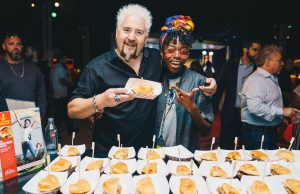 "Guy Fieri and psychology student Angelic Cox, the 2018 winner, show off ""The Jerk Man Burger,"" her original recipe."
