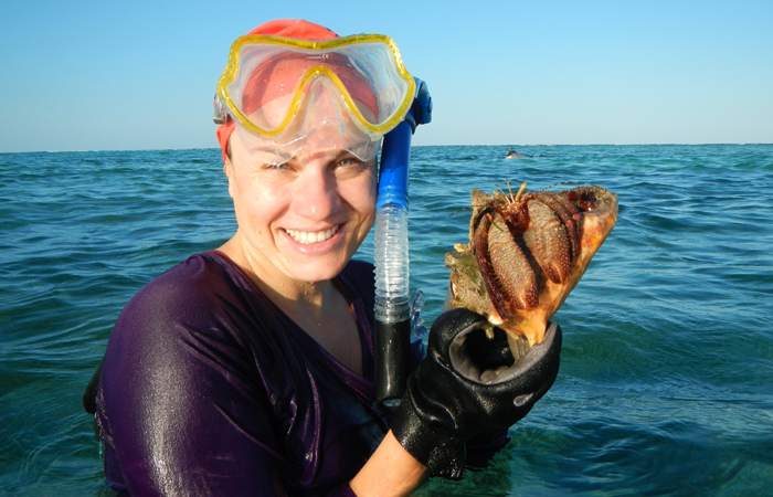 Heather Bracken-Grissom holds a hermit crab while conducting research in Carrie Bow Cay, Belize.