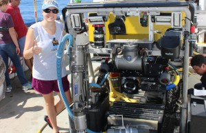 Heather Bracken-Grissom stands next to a remote operated vehicle aboard the Pelican to collect bioluminescent organisms and explore the deep sea.