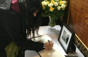 Ada Monserrat signs Stephen Hawking's book of condolences on behalf of FIU.