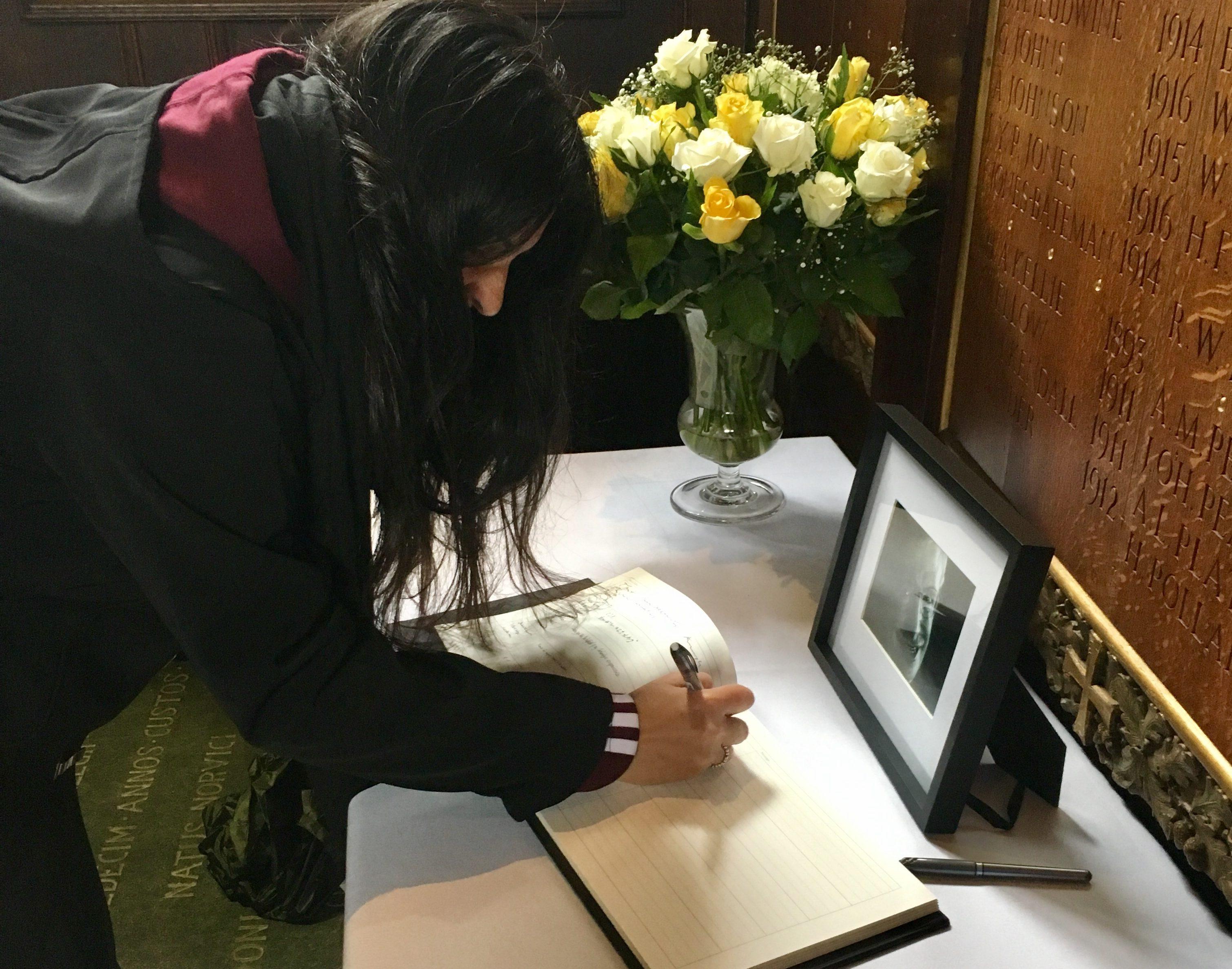 Ada Monserrat signs Stephen Hawking's book of condolences on behalf of FIU.