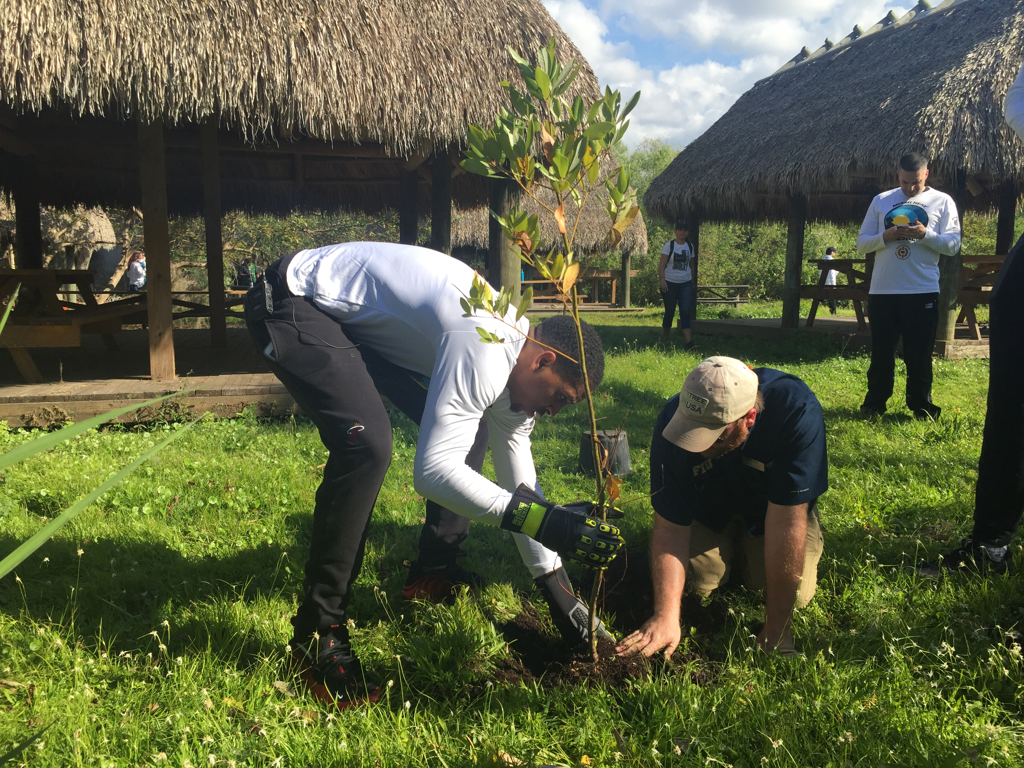 Miami Heat shooting guard Rodney McGruder (left) and FIU's Nick Ogle (right) plant environmentally appropriate and culturally important plants in the Everglades as part of Heat Glades Sweep.