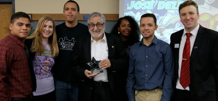 Jose Delbo accepts his award from the FIU Comics Club