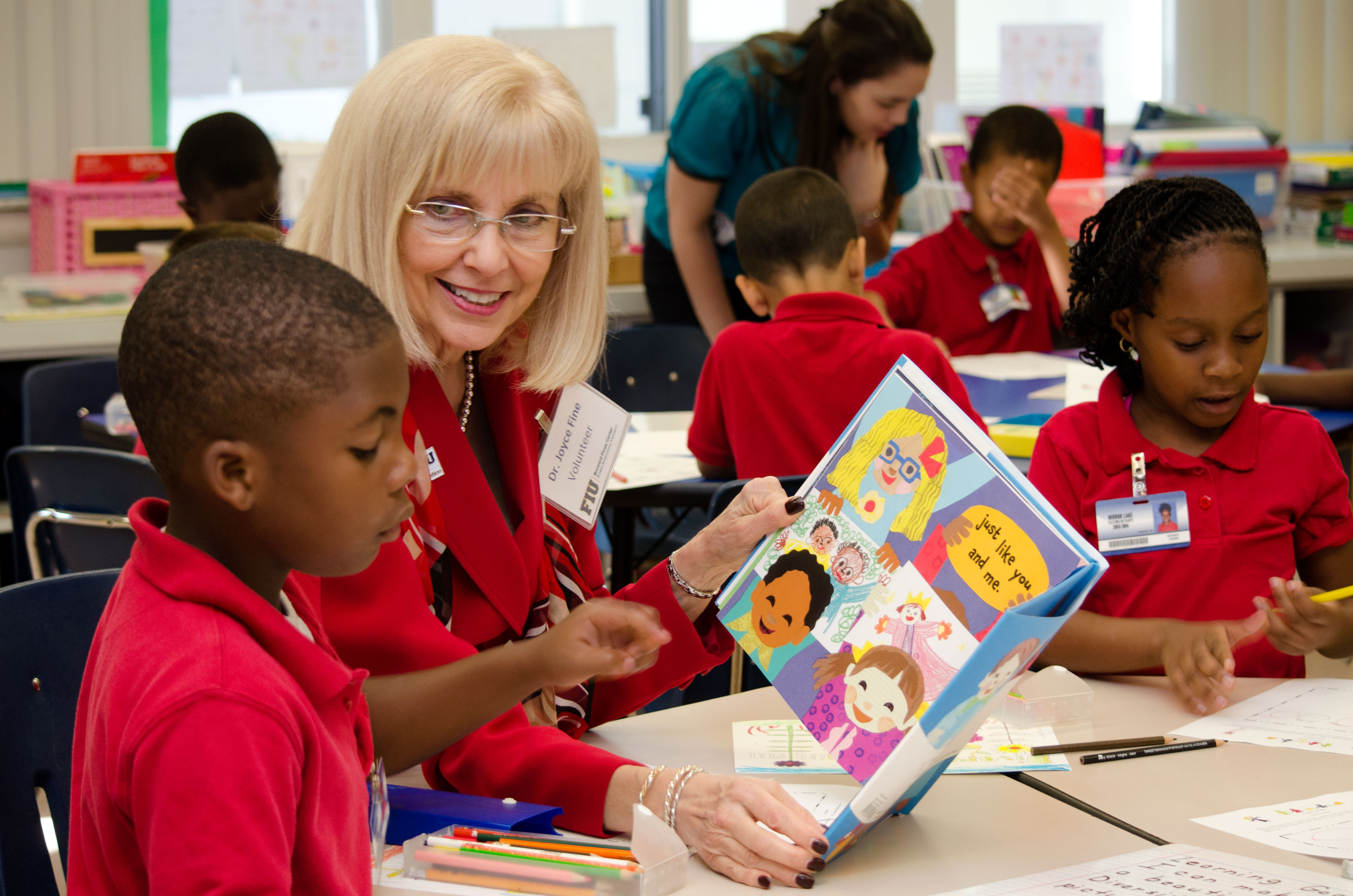 Associate Professor Joyce Fine, leader of the Reading Education Master's Program helps children at Mirror Lake Elementary learn to read.