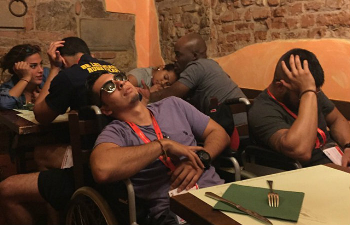 Juan Agudelo naps during dinner after spending a day touring Florence's cobblestone streets by wheelchair.
