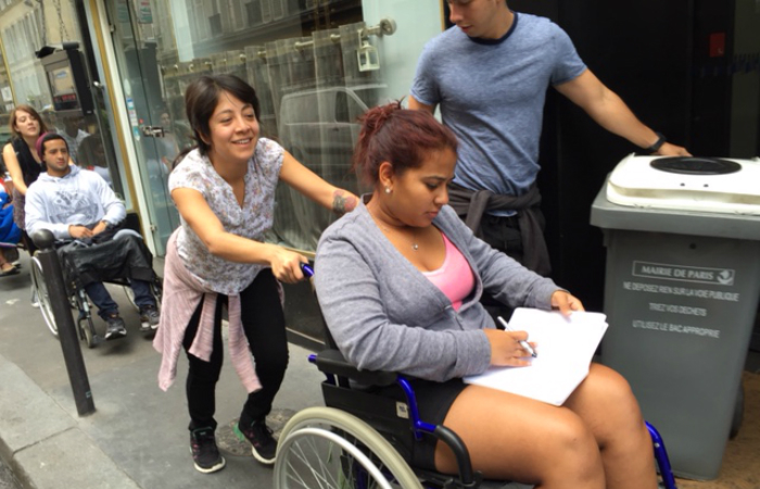 Kelsey Oslan is taken around Paris by wheelchair.