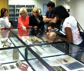 Elena Kurstin, in red, speaks with students and others who gathered to view some of the historic Cuban memorabilia she donated to FIU.