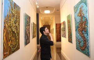 FIU student and City of Hialeah Emlpoyee Yordano Nicle observes Cortrada's Littorial Creatures Paintings