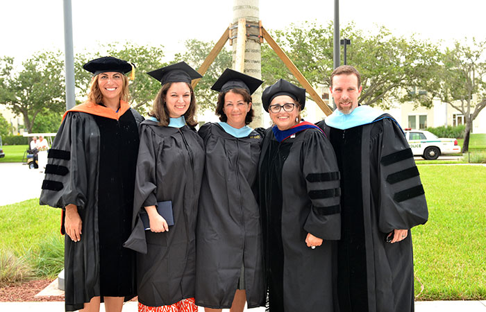 Associate Professor Elizabeth Cramer, online master's of special education graduates Dianelly Mouradian and Naomi Samole-Prager, Associate Professor Patricia M. Barbetta and Assistant Professor Kyle Bennett reunite before the College of Education's Aug. 3 commencement ceremony.