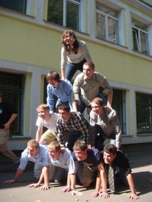 David Shor (in plaid shirt) and Leonard Foret (in row above Shor, wearing blue shirt) posing in a human pyramid in a group photo for the Math in Moscow program.