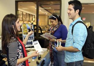 Natalie Castellanos, left, assists Florida International University student Roberto Gudino, right, during a healthcare enrollment event at FIU's Biscayne Bay Campus in North Miami in February. Photo Courtesy Miami Herald: http://www.miamiherald.com/news/health-care/article18717474.html#storylink=cpy