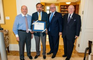 Jorge M. Perez, second from left, accepts a certificate in recognition of his $1 million gift for the Jorge Perez Metropolitan Center. Also pictured from left: Howard Lipman, CEO of the FIU Foundation, Inc., FIU President Mark B. Rosenberg and Green School Dean John F. Stack Jr.