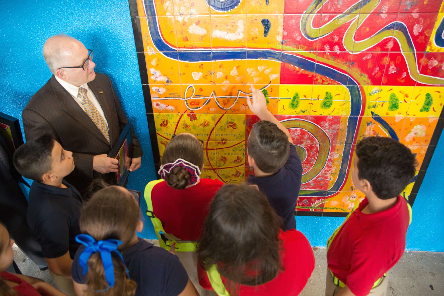 Sweetwater Elementary students explain the work that went into the mural to Rosenberg.