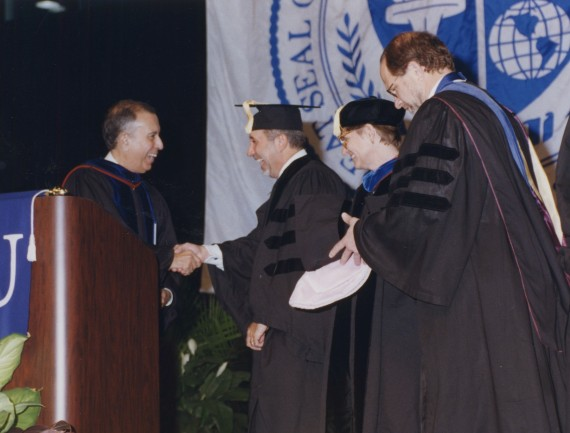 President Modesto A. Maidique (left) welcomes Emilio Estefan (second from left) to FIU to receive his honorary doctorate degree in business administration at the 1999 Fall Commencement ceremony.