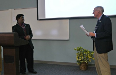 Arun Ramkissoon (left) answers a question from SRI Program Director Charles Bigger (right) during the mini-symposium presentation.