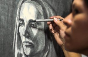 Student painter Lucia Morales studies every detail of a live model's face at FIU's Academy of Portrait & Figurative Art.