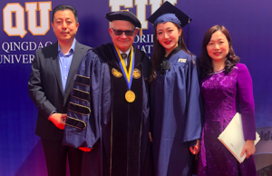 Class valedictorian Mengming Li and President Rosenberg are flanked by Li's parents.