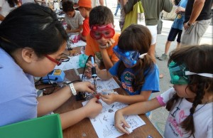 Charleotte Farolan, FIU CIS undergrad and Women in Computer Science president, assists children with their projects at the Miami Mini Maker Faire.