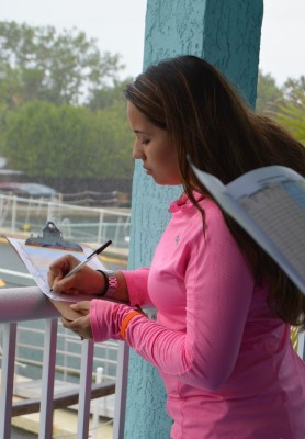 Junior biology major Stephany Matallana records data on a behavioral ethogram chart while observing dolphins interacting with their environment.