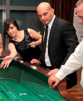 Maria Teresa Suarez YR tests Lady Luck at one of the gaming tables as co-worker Timothy Negron, watches.