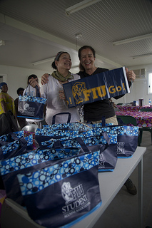 Graduate student Sabrina Diz and FIU Magazine Editor Deborah O'Neil prepare gift bags full of supplies for the women's clinic.