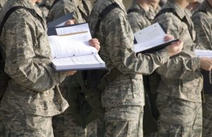 New military men stand with training manuals while attending an outdoor instructional period.
