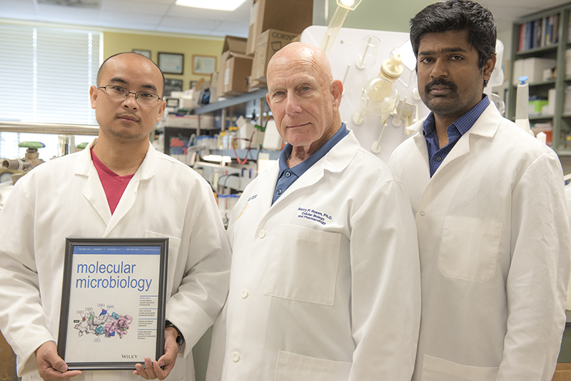 HWCOM researchers Jian Chen, Barry Rosen, and Venkadesh Nadar pose with journal cover featuring their study.