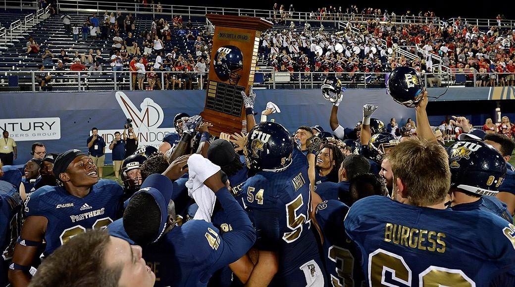 The FIU football team hoists the Don Shula Bowl Trophy as they celebrate their 33-31 victory over Florida Atlantic on Oct. 1.
